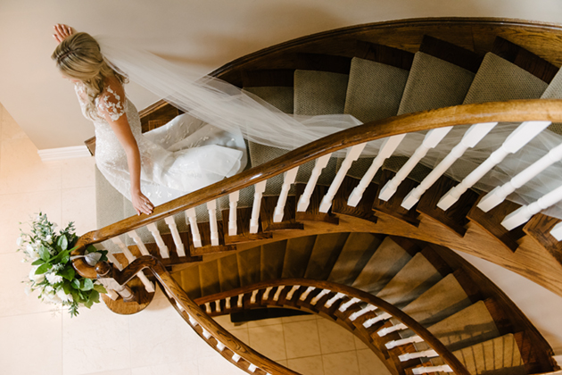A bride walking down the staircase for the big reveal
