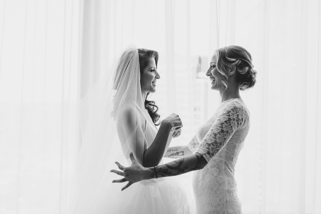 Nothing beats some sister love: a bride's smiling back to her sister as she adjust her veil before the ceremony