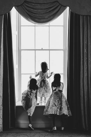 Cutest flower girls peeking through at wedding guests right before the wedding ceremony
