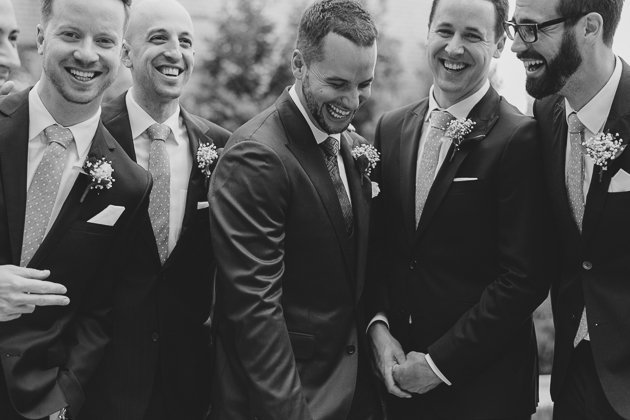Groom and his groomsmen having a fun time taking their wedding photos