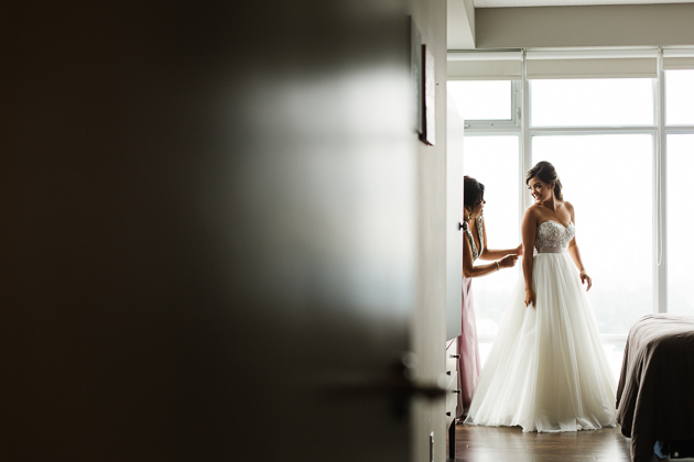 A mother-of-the-bride is helping her daughter put on her wedding dress