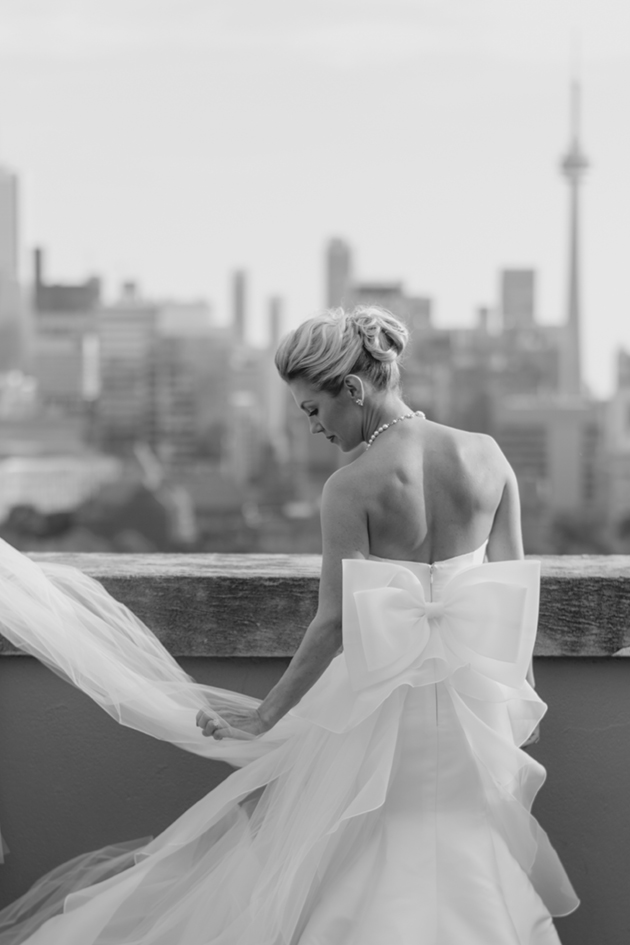 A bride fixing her dress right before the First Look on her wedding day at Park Hyatt Toronto