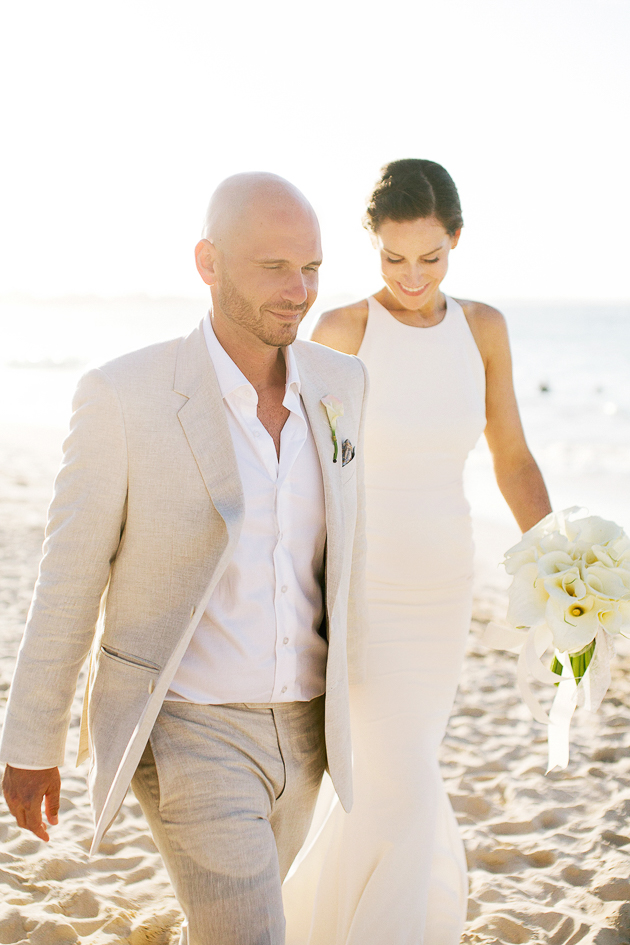 A bride and groom walking down the beach at a Royalton Punta Cana wedding