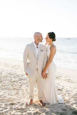 A bride and groom posing on a beach at their Royalton Punta Cana wedding