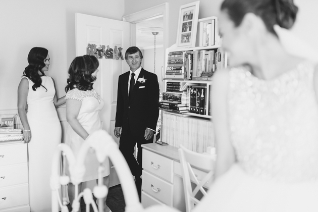 A father of the bride enters a room to see his daughter as a bride for the first time