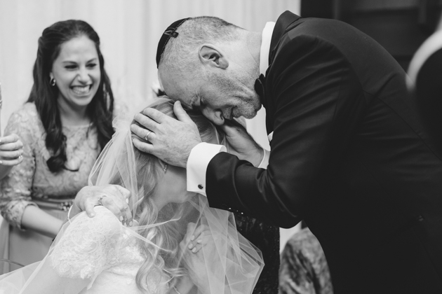 A father of the bride gives his daughter blessings after the wedding ceremony