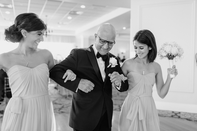 A father of the bride enters the wedding reception with his two daughters