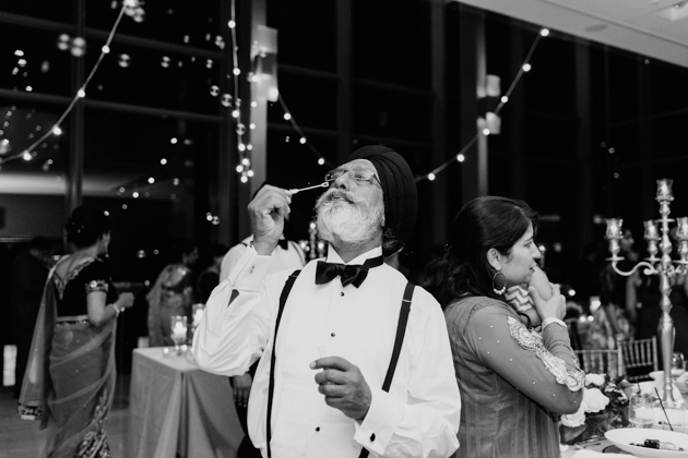 A father of the bride blowing soap bubbles during wedding reception