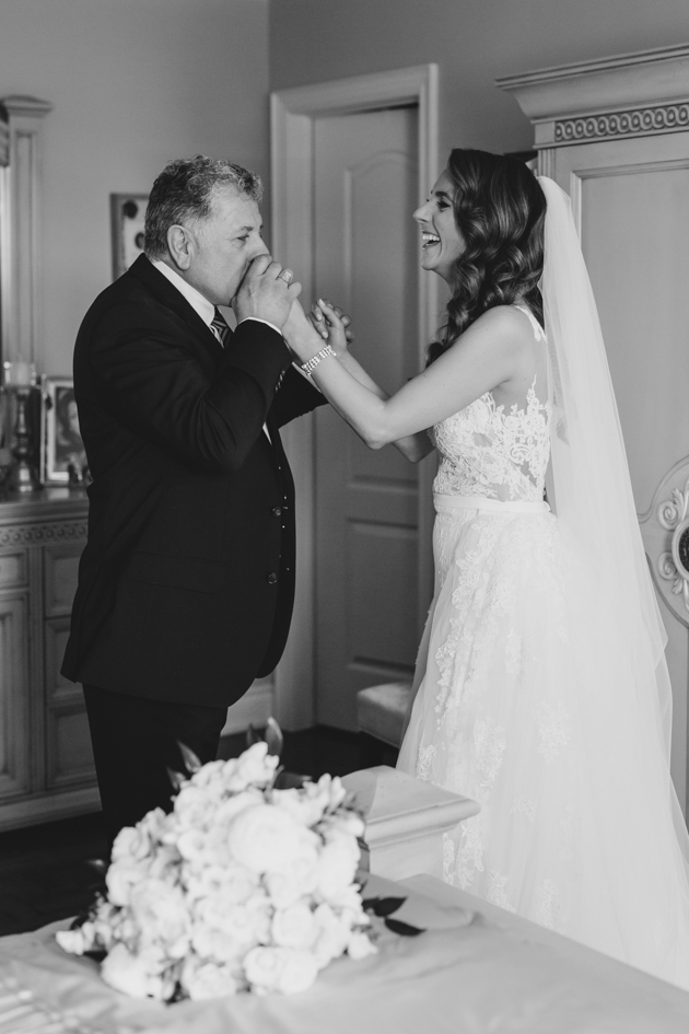 A father of the bride kisses his daughter as he sees her for the first time as a bride in the morning