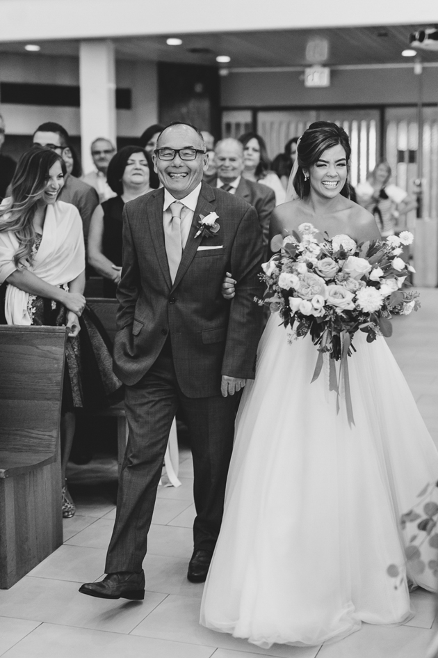A proud father walks his daughter down the aisle during the wedding ceremony