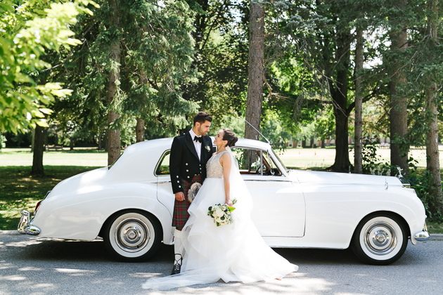 A bride and groom posing for their wedding portraits in front of the Glendon College