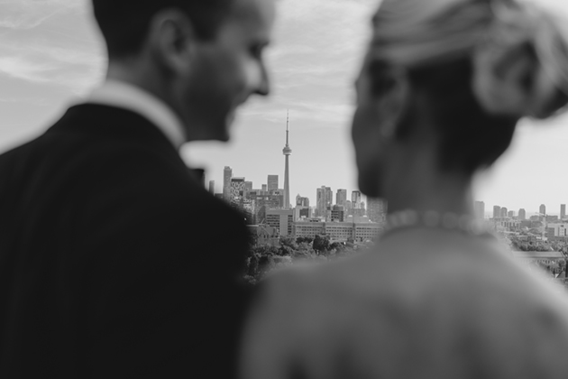 A bride and groom overlooking the CN tower on the rooftop of the Park Hyatt during their wedding portraits