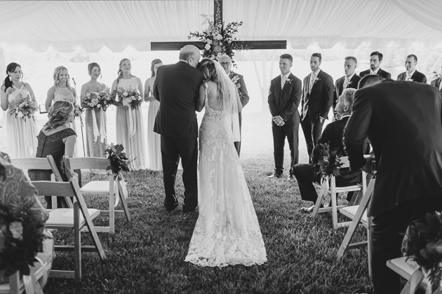 Father of the bride gives a bride a kiss on her head before he gives her away during the wedding ceremony