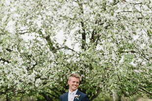 A groom's portrait among the apple blooms