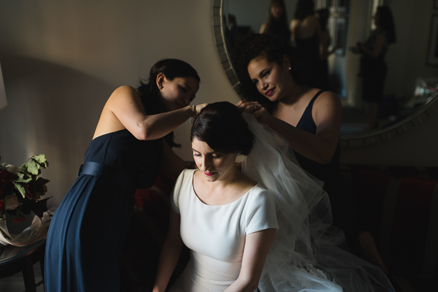 Bridesmaids help a bride to put on her veil at the King Edward Hotel