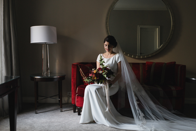 A bride looking at her flowers at the King Edward Hotel