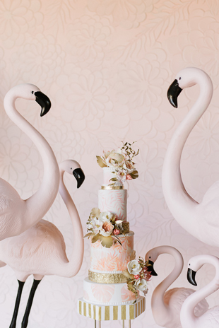 Pink wedding theme inspiration featuring a floral cake and pink flamingoes!