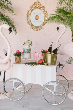 Pink wedding theme inspiration featuring flamingoes and champaign cart