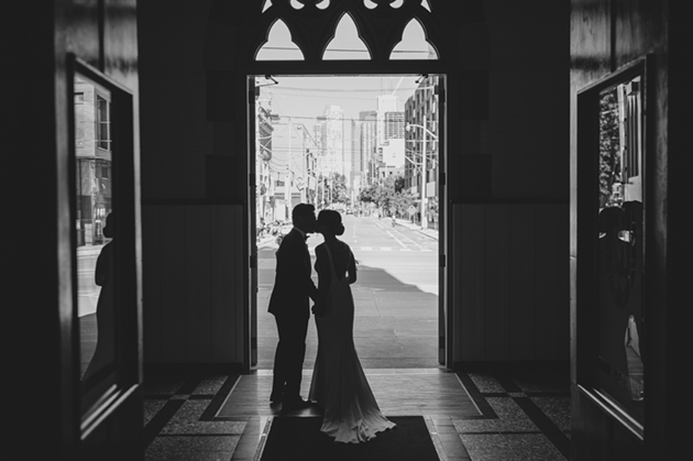 A bride and groom kiss before exiting the church
