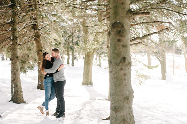 A couple taking their winter engagement photos in the snow