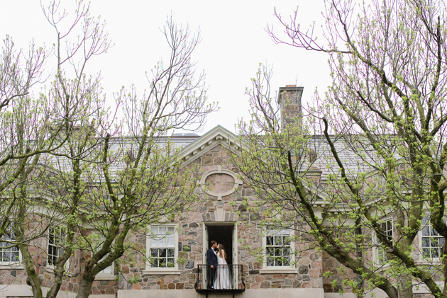A bride and groom kissing on the Graydon Hall balcony