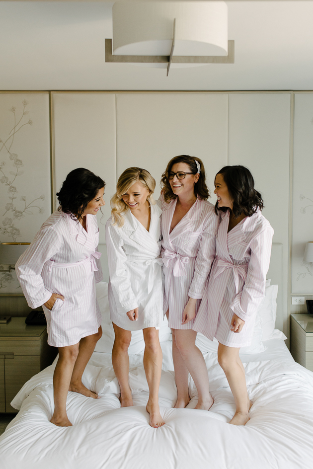 Bridesmaids jumping on the bed on the morning of the wedding at Four Seasons Hotel Toronto
