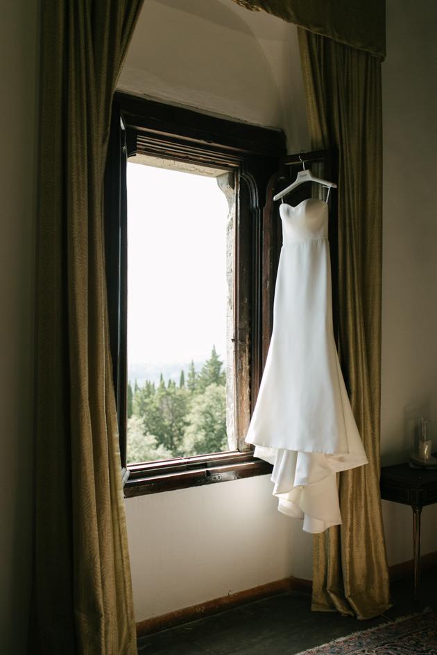 Bride's dress hangs from window of Castello di Vincigliata