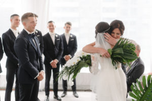 Bride hugs her mother at the end of the aisle