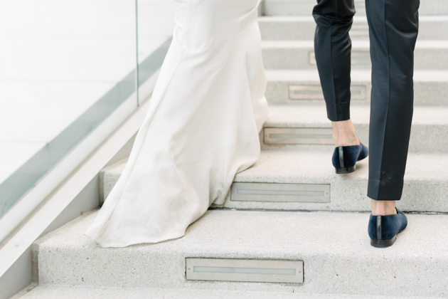 Bride and groom walk up the stairs