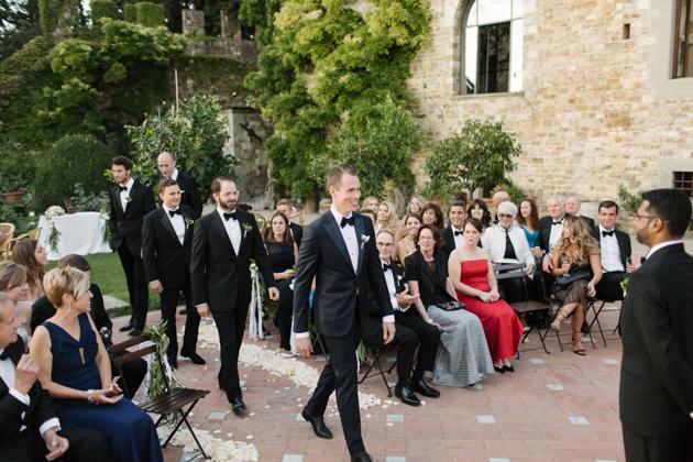 Groom and groomsmen walk down the aisle at the Castello di Vincigliata