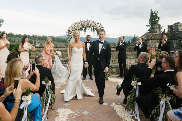 Bride and groom walk down the aisle at the Castello di Vincigliata