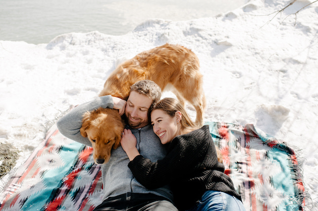 A couple taking their winter engagement photos on a blanket with their dog in the snow